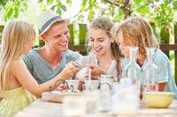 Familie im Garten beim Kaffee trinken