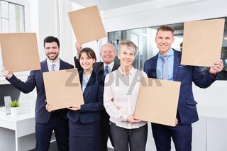 Business Team hält leere Schilder im Büro