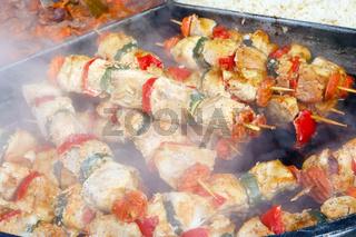 fried  smoked pork on wooden skewers  on a big steel  frying pan