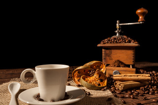 Coffee cup, dried orange fruit, cinnamon sticks and coffee grinder