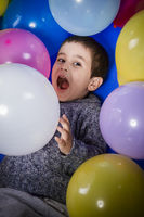 Brunette boy playing with a lot of colorful balloons, smiles and joy at birthday party