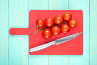 Tomatoes and knife on a red cutting board