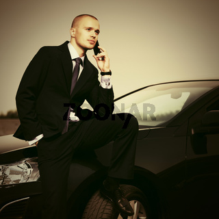 Young handsome businessman calling on phone sitting on his car