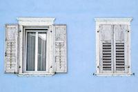 Zwei Fenster mit Fensterläden in einem blauen Haus