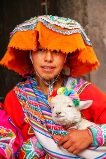Young woman in traditional dress holding lamb in the street of Cusco, Peru