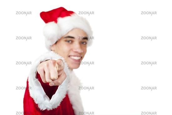 Lachender Jugendlicher als Weihnachtsmann zeigt mit Finger