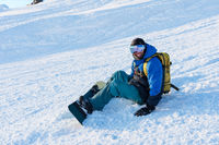 Smiling man snowboarder resting sit