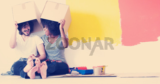 young multiethnic couple playing with cardboard boxes