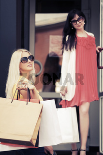 Two young fashion women with shopping bags in the mall doorway