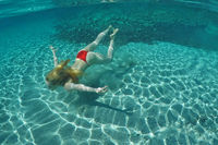 Young woman swims at the bottom of an exotic beach on underwater view