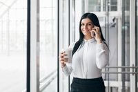 Successful confident young business woman with coffee and smartphone in an office setting