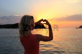 Mädchen mit Herzsymbol am Hafen