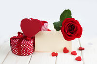 Rose, hearts and card on table