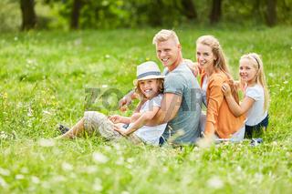 Familie mit zwei Kindern auf einer Wiese