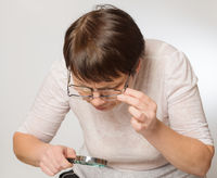 Elderly woman looks at something through two glasses and a magnifying glass