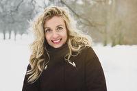 woman enjoying a winter walk through snow covered park