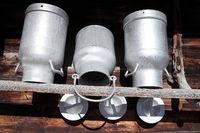 drei alte Milchkannen im Regal