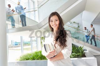 Glückliche asiatische Studentin mit Büchern