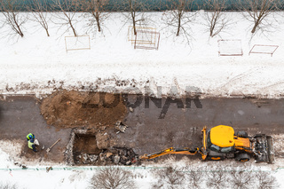 top view of workers and excavator digging road