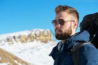 A hipster traveler with a beard wearing sunglasses in nature.