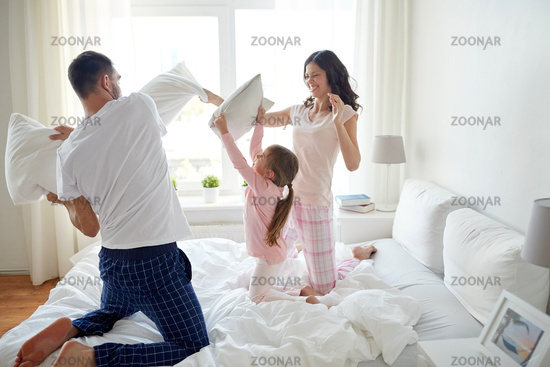 happy family having pillow fight in bed at home