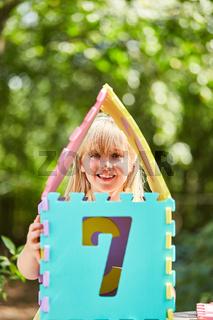Mädchen baut aus bunten Puzzleteilen ein Haus