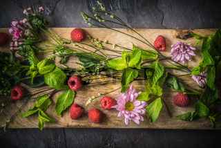 Flowers  , raspberries and mint on the wooden board  top view