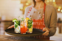 Young pretty woman with red and green cocktails on tray