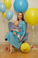 One year old baby boy first birthday. Toddler child with mother sitting in chair