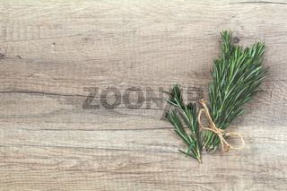 Rosemary bunch of bouquets on light wooden surface. Top view, copy space.