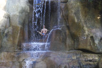 Man meditating under waterfall