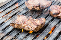 Beef steaks on grill with flames.