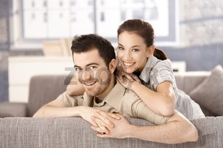 Young couple smiling happily on sofa at home