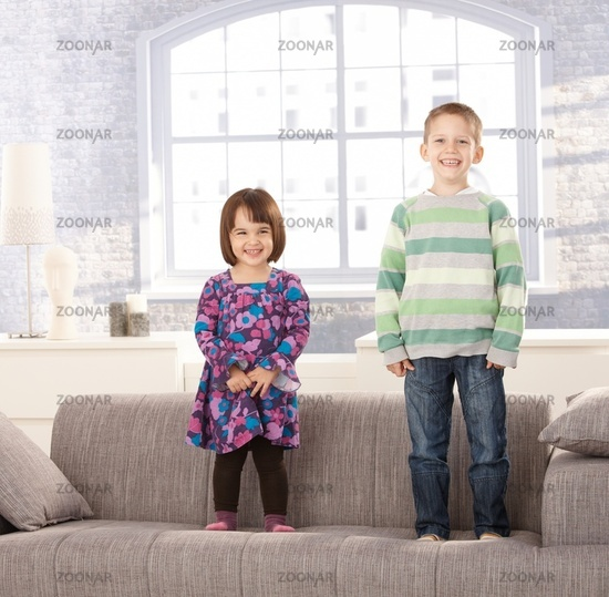 Laughing kids standing on couch