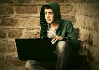 Young man using laptop on the steps
