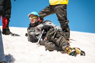 A mountaineer in a sunny spot and professional equipment lying resting on a snowy slope surrounded by his comrades