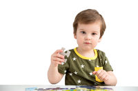 Little boy playing puzzle on a white background