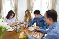 Happy young friends playing board game together
