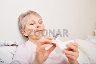 Kranke Seniorin mit Tablettenspender