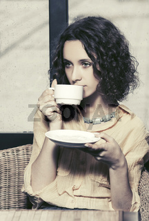 Sad young fashion woman drinking tea at restaurant