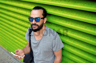 man in sunglasses with smartphone and bag at wall