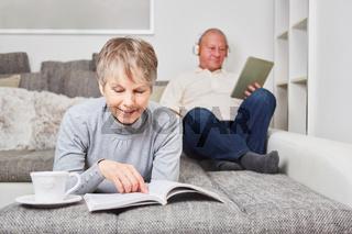 Frau als Seniorin liest zuhause ein Buch