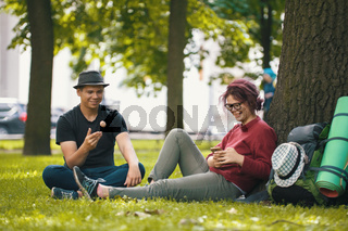 Young students - boy and girl with backpacks after hiking have a rest in the park