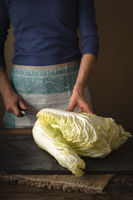 Woman cuts Chinese cabbage on a gray slate