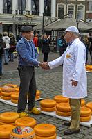 Bauer und Käsehändler feilschen um den Preis für Gouda Käse per Handschlag, Gouda, Niederlande