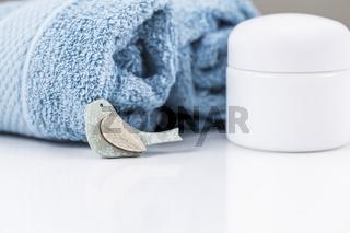 Eine Cremedose, neben Handtüchern und Dekoration, eine Nahaufnahme