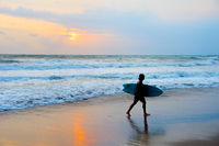 Surfer at beach with surfboard