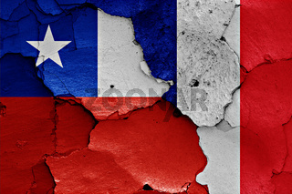 flags of Chile and France painted on cracked wall