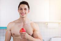 Gesunde Ernährung junger Bodybuilder Mann Textfreiraum Essen Apfel Frucht Obst in der Küche