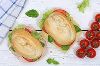 Brötchen Sandwich Baguette belegt mit Käse und Schinken von oben auf Holzbrett